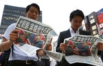 People look at the extra edition of  Japanese newspaper Mainichi Shimbun reporting the summit between U.S. President Donald Trump and North Korean leader Kim Jong Un in Singapore, at Shimbashi Station in Tokyo, Tuesday, June 12, 2018.  The headline reads: North Korea promises to denuclearize. (Suo Takekuma/Kyodo News via AP)