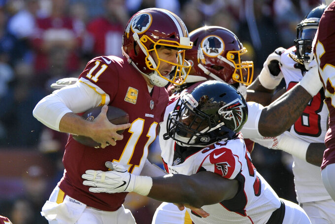 FILE - In this Nov. 4, 2018, file photo, Washington Redskins quarterback Alex Smith, left, is sacked by Atlanta Falcons defensive tackle Grady Jarrett during an NFL football game in Landover, Md. The Falcons have agreed to terms with Jarrett on a four-year contract extension before the NFL deadline for franchise-tagged players. (AP Photo/Mark Tenally, File)