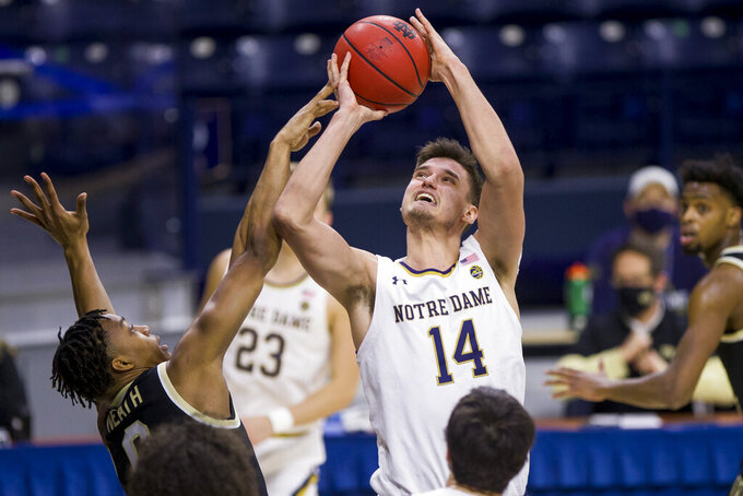 Notre Dame's Nate Laszewski (14) shoots as Wake Forest's Jahcobi Neath (0) defends during the first half of an NCAA college basketball game Tuesday, Feb. 2, 2021, in South Bend, Ind. (AP Photo/Robert Franklin)