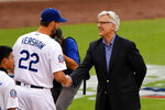 FILE - In this March 31, 2018, file photo, Los Angeles Dodgers' Clayton Kershaw (22) shakes hands with co-owner Mark Walter as he receives his National League Championship ring during a ceremony prior to the team's baseball game against the San Francisco Giants in Los Angeles. The Dodgers were named the Sports Humanitarian Team of the Year at the ESPY Awards on Sunday, June 21, 2020, for their foundation that works to improve education, health care, homelessness and social justice in the city. The foundation, of which Walter is chairman, will use the $100,000 award to continue its programs. (AP Photo/Mark J. Terrill, File)