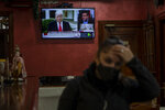 A waiter gestures in front a TV screen broadcasting news reports on U.S. President Donald Trump, in Rivas Vaciamadrid, Spain, Thursday, Jan. 7, 2021. Congress confirmed Democrat Joe Biden as the presidential election winner early Thursday after a violent mob loyal to President Donald Trump stormed the U.S. Capitol in a stunning attempt to overturn America's presidential election. (AP Photo/Manu Fernandez)