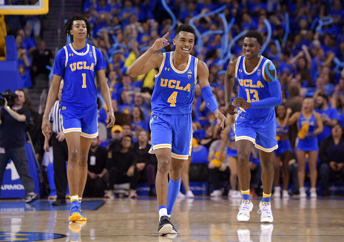 FILE - In this Feb. 28, 2019, file photo, UCLA guard Jaylen Hands, center, celebrates after hitting a 3-point shot as center Moses Brown, left, and guard Kris Wilkes follow during the second half of the teams' NCAA college basketball game against Southern California in Los Angeles. UCLA won 93-88 in overtime. . The Bruins' sophomore guard has been one of the conference's best players all season and was named player of the week after finishing with 21 points and 10 assists in UCLA's win over rival USC. (AP Photo/Mark J. Terrill, File)