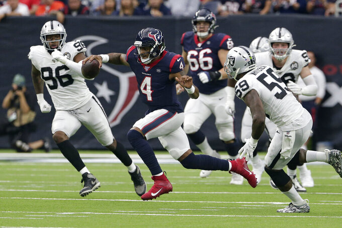 Houston Texans quarterback Deshaun Watson (4) scrambles as Oakland Raiders defensive end Clelin Ferrell (96) and outside linebacker Tahir Whitehead (59) close in during the first half of an NFL football game Sunday, Oct. 27, 2019, in Houston. (AP Photo/Michael Wyke)