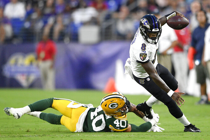 Baltimore Ravens quarterback Lamar Jackson, right, avoids a hit fromGreen Bay Packers linebacker Curtis Bolton during the first half of a NFL football preseason game, Thursday, Aug. 15, 2019, in Baltimore. (AP Photo/Nick Wass)