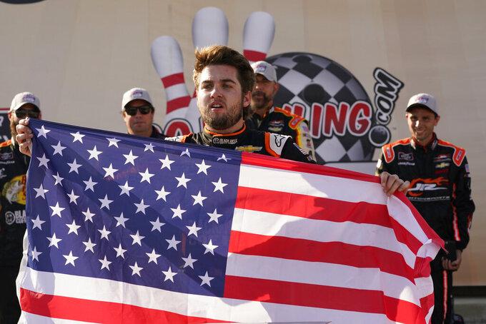 Noah Gragson (9) displays a U.S. flag as he celebrates winning the NASCAR Xfinity auto race in Richmond, Va., Saturday, Sept. 11, 2021. (AP Photo/Steve Helber)