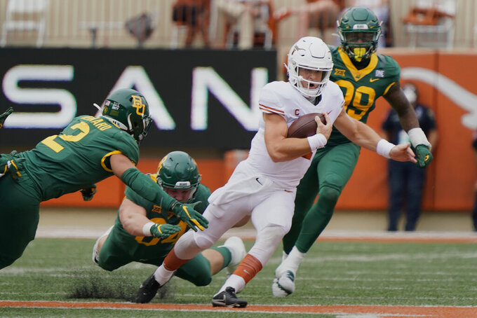 Texas' Sam Ehlinger (11) runs for a first down past Baylor's Terrel Bernard (2) during the first half of an NCAA college football game in Austin, Texas, Saturday, Oct. 24, 2020. (AP Photo/Chuck Burton)