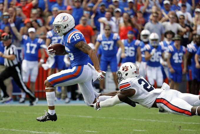 Florida wide receiver Freddie Swain (16) outruns a tackle by Auburn defensive back Daniel Thomas on his way to a 64-yard touchdown during the first half of an NCAA college football game, Saturday, Oct. 5, 2019, in Gainesville, Fla. (AP Photo/John Raoux)