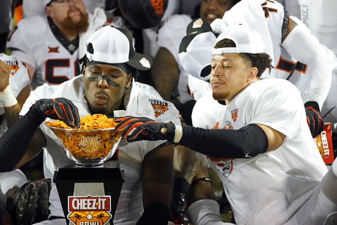Oklahoma State linebacker Amen Ogbongbemiga, left, and linebacker Relijah Sherman enjoy some Cheez-It's from the championship trophy after winning the Cheez-It Bowl NCAA college football game against Miami, Tuesday, Dec. 29, 2020, in Orlando, Fla. (AP Photo/John Raoux)