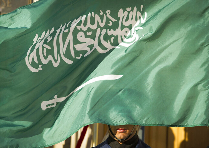 FILE - In this March 22, 2018, file photo, an honor guard member is covered by the flag of Saudi Arabia, in Washington. Saudi Arabia, for years one of the world's most prolific executioners, dramatically reduced the number of people put to death in 2020, following changes halting executions for non-violent drug-related crimes, according to the government's tally and independent observers. (AP Photo/Cliff Owen, File)