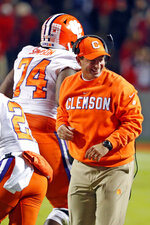 Clemson head coach Dabo Swinney congratulates Clemson's John Simpson (74) during the first half of an NCAA college football game against North Carolina State in Raleigh, N.C., Saturday, Nov. 9, 2019. (AP Photo/Karl B DeBlaker)