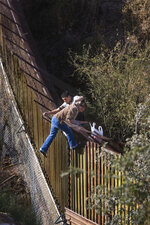 In this Dec. 20 2008, photo taken by Arizona Republic photographer Nick Oza, a woman crosses the border fence from Nogales, Mexico, into the United States, with a man believed to be a smuggler, known as a coyote. Pulitzer Prize-winning photojournalist Oza, who documented the lives of disaster victims and immigrants, died Monday, Sept. 27, 2021, after being hospitalized more than three weeks with serious injuries from a traffic accident. He was 57. (Nick Oza/The Arizona Republic via AP)