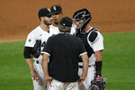Chicago White Sox pitching coach Don Cooper, center talks with starting pitcher Dylan Cease, left, while catcher James McCann, right and Jose Abreu listen, during the fifth inning of a baseball game against the Cleveland Indians Friday, Aug. 7, 2020, in Chicago. (AP Photo/Charles Rex Arbogast)