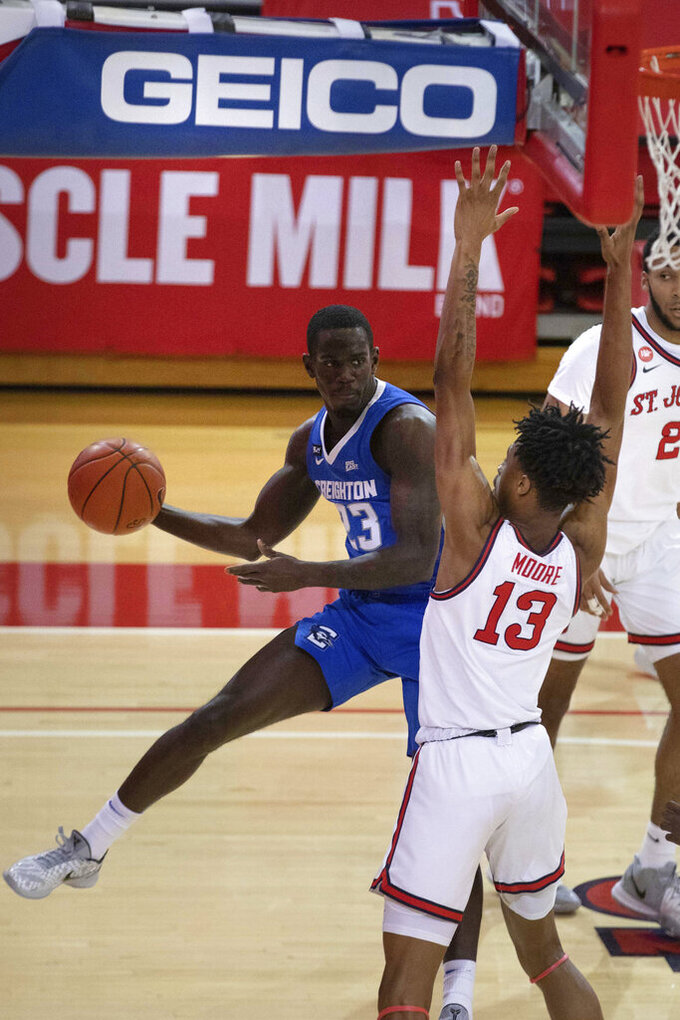 St. John's forward Isaih Moore, right, blocks Creighton forward Damien Jefferson in the first half of an NCAA college basketball game Thursday, Dec. 17, 2020, in New York. (AP Photo/Kevin Hagen)