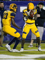 Kent State wide receiver Isaiah McKoy (23) watches as wide receiver Antwan Dixon (10) celebrates scoring a touchdown during the second half against Utah State in the Frisco Bowl NCAA college football game Friday, Dec. 20, 2019, in Frisco, Texas. Kent State won 51-41. (AP Photo/Brandon Wade)