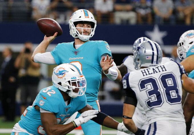 Miami Dolphins quarterback Josh Rosen (3) throws a pass as running back Kenyan Drake (32) provides protection as Dallas Cowboys' Jeff Heath (38) rushes in the first half of a NFL football game in Arlington, Texas, Sunday, Sept. 22, 2019. (AP Photo/Michael Ainsworth)