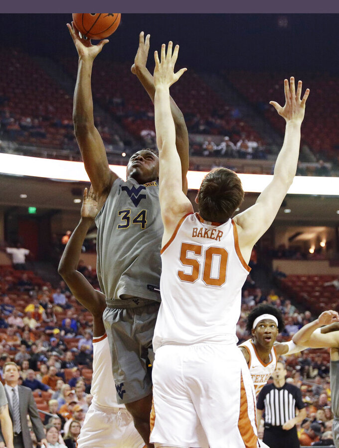 West Virginia forward Oscar Tshiebwe (34) shoots over Texas center Will Baker (50) during the first half of an NCAA college basketball game, Monday, Feb. 24, 2020, in Austin, Texas. (AP Photo/Eric Gay)