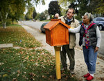 In this Oct. 22, 2013 photo Little Free Libraries creator Todd Bol, left, and Eddye Watkins, whose yard the library was erected in, place decorative pieces atop the Amish made, wooden library in Minneapolis. Bol, who founded Little Free Library, the boxes of books for sharing that popped up across the U.S. and spread to more than 80 countries, has died. Bol died Thursday, Oct. 18, 2018, in a Minnesota hospice of complications from pancreatic cancer, according to Little Free Library spokeswoman Margret Aldrich. He was 62.  (David Joles/Star Tribune via AP)