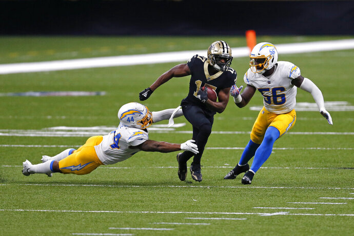 New Orleans Saints wide receiver Emmanuel Sanders (17) carries on a reception between Los Angeles Chargers outside linebacker Kyzir White (44) and linebacker Kenneth Murray (56) in the second half of an NFL football game in New Orleans, Monday, Oct. 12, 2020. (AP Photo/Brett Duke)