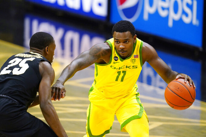 Oregon guard Amauri Hardy, right, drives to the basket as Colorado guard McKinley Wright IV defends in the first half of an NCAA college basketball game Thursday, Jan. 7, 2021, in Boulder, Colo. (AP Photo/David Zalubowski)