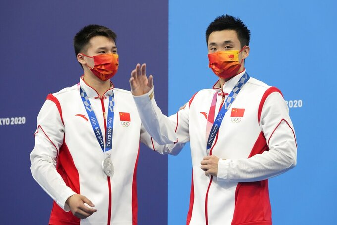 Yuan Cao and Aisen Chen of China react after winning silver medals during the men's synchronized 10m platform diving final at the Tokyo Aquatics Centre at the 2020 Summer Olympics, Monday, July 26, 2021, in Tokyo, Japan. (AP Photo/Dmitri Lovetsky)