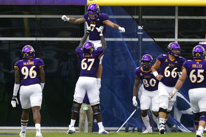 East Carolina offensive lineman D'Ante Smith (67) lifts running back Darius Pinnix Jr. (7) following Pinnix's touchdown against Central Florida during the first half of an NCAA college football game in Greenville, N.C., Saturday, Sept. 26, 2020. (AP Photo/Gerry Broome)