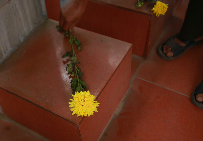 In this Feb. 16, 2019, photo, veteran Duong Van Dau places flowers at a memorial for North Korean fallen pilots in Bac Giang province, Vietnam. The fourteen headstones of the pilots who died while fighting American bombers alongside the Vietnamese army during the Vietnam war remain as a symbol of Vietnam-North Korea friendship. (AP Photo/Hau Dinh)