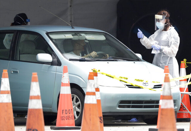 A healthcare worker gives a thumbs up to a driver as he stops his car, Wednesday, Aug. 5, 2020, at a COVID-19 testing site outside Hard Rock Stadium in Miami Gardens, Fla. State officials say Florida has surpassed 500,000 coronavirus cases. Meanwhile, testing is ramping up following a temporary shutdown of some sites because of Tropical Storm Isaias. (AP Photo/Wilfredo Lee)