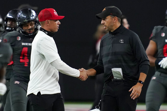 UNLV head coach Marcus Arroyo, left, shakes hands with Iowa State head coach Matt Campbell after an NCAA college football game Saturday, Sept. 18, 2021, in Las Vegas. (AP Photo/John Locher)