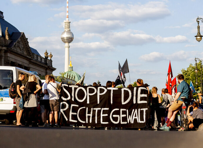 File---Picture taken June 18, 2019 shows people attending a protest ralley in Berlin, Germany, against far right violence. German police are investigating a series of threats sent to officials and institutions days after the arrest of a far-right extremist on suspicion of killing a pro-migrant politician. Slogan reads 'Stop Far Right Violence' (Christoph Soeder/dpa via AP)
