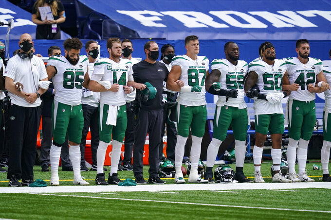 Members of the New York Jets link arms during the National Anthem before an NFL football game against the Indianapolis Colts in Indianapolis, Sunday, Sept. 27, 2020. (AP Photo/Darron Cummings)