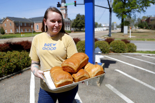In this Thursday, March 26, 2020 photo, Laura Hallmark, owner of Strange Brew Coffeehouse, poses with loafs of bread she and her team made at the store in Tupelo Miss. The coffeehouse has added to its production of coffee and pastries by making fresh loafs of bread made from scratch to help with the demand of empty shelves at the groceries stores during the coronavirus outbreak. (AP Photo/Julio Cortez)