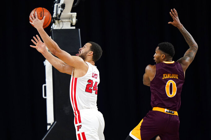 Fairfield's Jesus Cruz left, goes up for a shot past Iona's Berrick JeanLouis in the first half of an NCAA college basketball game during the finals of the Metro Atlantic Athletic Conference tournament, Saturday, March 13, 2021, in Atlantic City, N.J. (AP Photo/Matt Slocum)