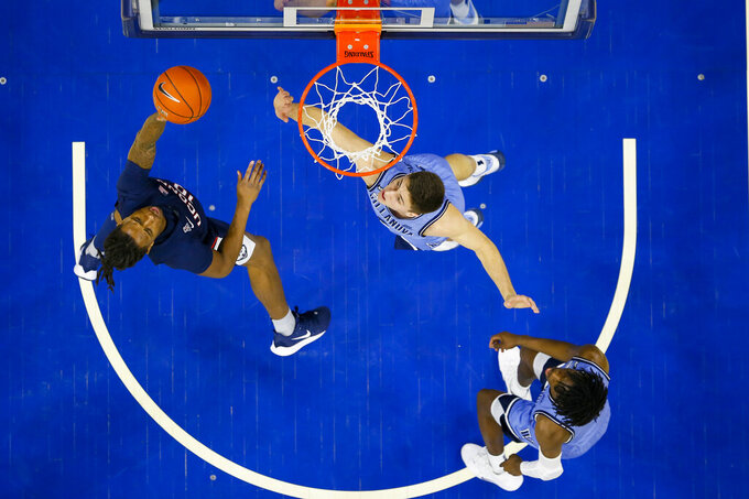 Connecticut's Brendan Adams, left, shoots the ball with Villanova's Cole Swider, center, defending during the first half of an NCAA college basketball game Saturday, Jan. 18, 2020, in Philadelphia. (AP Photo/Chris Szagola)
