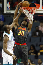 Atlanta Hawks' Damian Jones (30) dunks on Charlotte Hornets' Bismack Biyombo (8) during the first half of an NBA basketball game in Charlotte, N.C., Sunday, Dec. 8, 2019. (AP Photo/Bob Leverone)