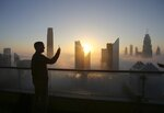 FILE- In this Saturday, Dec. 31, 2016 file photo, a man takes a photo as the sun rises over the city skyline from a balcony on the 42nd floor of a hotel on a foggy day in Dubai, United Arab Emirates.  In an unmarked villa, nestled amid homes in an upscale Dubai neighborhood, sits the first fully functioning synagogue in the Arabian Peninsula in decades.  Though its members keep its precise location secret, the synagogue's existence and the tacit approval it has received from this Islamic sheikhdom represents a slow rebirth of a burgeoning Jewish community in the Persian Gulf uprooted over the decades after the creation of Israel.  (AP Photo/Kamran Jebreili, File)