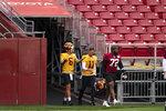 Washington quarterback Steven Montez (6), quarterback Alex Smith (11), and defensive end James Smith-Williams (72) walk on the field for an NFL football practice at FedEx Field, Monday, Aug. 31, 2020, in Washington. (AP Photo/Alex Brandon)