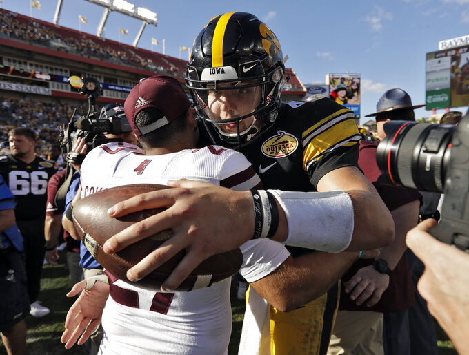 Iowa quarterback Nate Stanley, right, hugs Mississippi State punter Kody Schexnayder after Iowa defeated Mississippi State 27-22 during the Outback Bowl NCAA college football game Tuesday, Jan. 1, 2019, in Tampa, Fla. (AP Photo/Chris O'Meara)