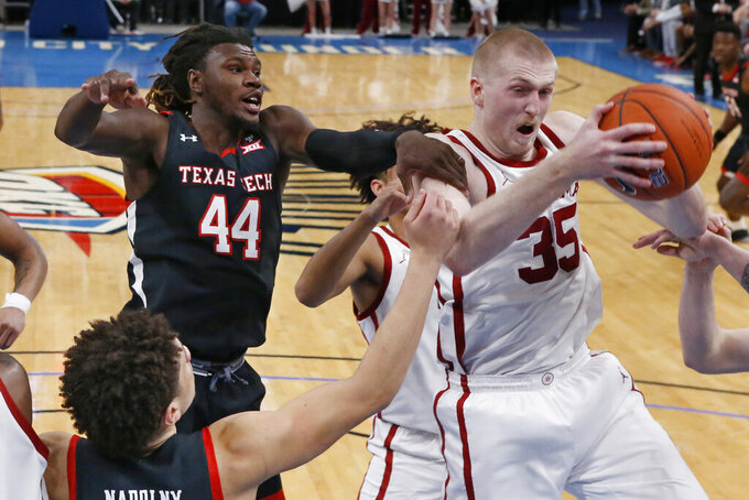 Oklahoma forward Brady Manek (35) grabs a rebound in front of Texas Tech guard Chris Clarke (44) and guard Clarence Nadolny, left, in the second half of an NCAA college basketball game Tuesday, Feb. 25, 2020, in Oklahoma City. (AP Photo/Sue Ogrocki)