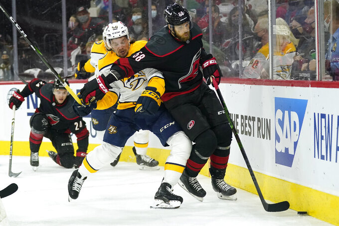 Nashville Predators left wing Erik Haula (56) and Carolina Hurricanes defenseman Jani Hakanpaa (58) skate for the puck during the first period in Game 1 of an NHL hockey Stanley Cup first-round playoff series in Raleigh, N.C., Monday, May 17, 2021. (AP Photo/Gerry Broome)