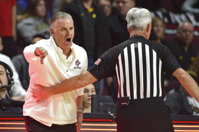 San Diego State coach Brian Dutcher is held back by a referee as he calls to his team during the first half of an NCAA college basketball game against Iowa Friday, Nov. 29, 2019, in Las Vegas. (AP Photo/David Becker)