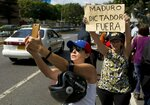 An opposition member take a selfie beside to a woman holding up a sign that reads in Spanish