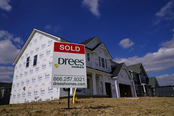 "FILE - In this Sept. 25, 2020 file photo, a ""sold"" sign sits on a lot as new home construction continues in Westfield, Ind. Mortgage rates fell for the first time in more than two months as buyers continue to be stifled by high prices and limited supply. (AP Photo/Michael Conroy, File)"