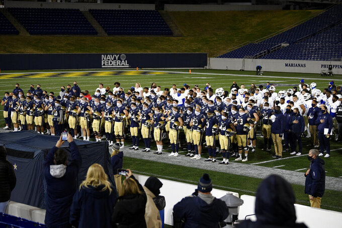 Navy and Tulsa stand team members stand on the field after an NCAA college football game Saturday, Dec. 5, 2020, in Annapolis, Md. Tulsa won 19-6. (AP Photo/Nick Wass)
