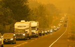 A steady stream of vehicles heads west on a road east of Springfield, Ore., as residents evacuate the area ahead of a fast-moving wildfire Tuesday Sept. 8, 2020. (Chris Pietsch/The Register-Guard via AP)