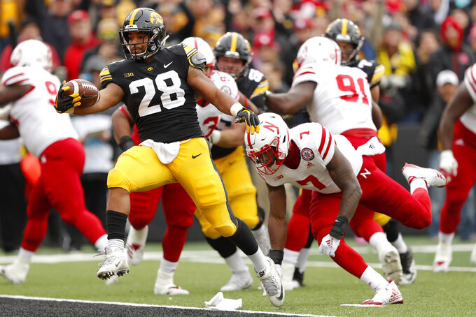 Iowa running back Toren Young (28) runs from Nebraska linebacker Mohamed Barry (7) during a 4-yard touchdown run in the first half of an NCAA college football game, Friday, Nov. 23, 2018, in Iowa City, Iowa. (AP Photo/Charlie Neibergall)