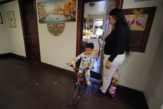 FILE - In this March 10, 2021, file photo, Isabel Miranda's 4-year-old son, Julian, rides his bike into the hallway of their rental apartment in Haverhill, Mass. A federal judge has ruled, Wednesday, May 5, 2021, that the Centers for Disease Control exceeded its authority when it imposed a federal eviction moratorium to provide protection for renters out of concern that having families lose their homes and move into shelters or share crowded conditions with relatives or friends during the pandemic would further spread the highly contagious virus. Miranda and her family would no longer have this eviction protection if this ruling stands. (AP Photo/Elise Amendola, File)
