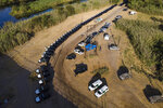 A line of Texas Department of Safety vehicles lines the bank of the Rio Grande near an encampment of migrants, many from Haiti, Wednesday, Sept. 22, 2021, in Del Rio, Texas.   (AP Photo/Julio Cortez)