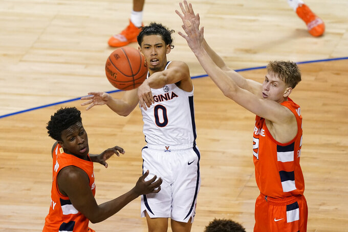 Virginia guard Kihei Clark (0) passes the ball in front of Syracuse forward Kadary Richmond, left, and Syracuse forward Marek Dolezaj, right, during the second half of an NCAA college basketball game in the quarterfinal round of the Atlantic Coast Conference tournament in Greensboro, N.C., Thursday, March 11, 2021. (AP Photo/Gerry Broome)