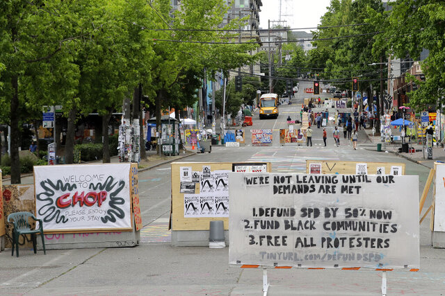 A sign on the street welcomes visitors and a list of demands is posted Wednesday, June 24, 2020, inside the CHOP (Capitol Hill Occupied Protest) zone in Seattle. The area has been occupied since a police station was largely abandoned after clashes with protesters, but Seattle Mayor Jenny Durkan said Monday that the city would move to wind down the protest zone following several nearby shootings and other incidents that have distracted from changes sought peaceful protesters opposing racial inequity and police brutality. (AP Photo/Ted S. Warren)