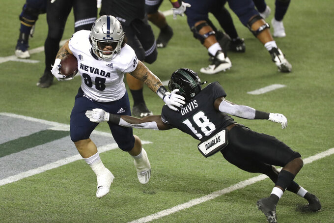 Nevada running back Toa Taua (35) brushes past Hawaii defensive back Cortez Davis (18) during the first half of an NCAA college football game Saturday, Nov. 28, 2020, in Honolulu. (AP Photo/Marco Garcia)